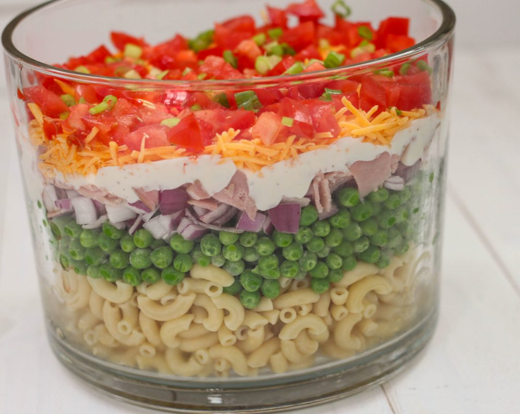 This is an easy and beautiful salad that makes the perfect side dish to bring to a potluck. Layered Pasta Salad has layers of macaroni, red onion, peas, ham, cheese, tomato and is tossed in a ranch dressing.